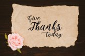 Photo top view of aged paper with give thanks today lettering and rose flower on wooden table