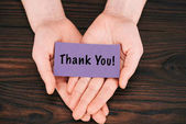 Photo cropped shot of woman holding purple paper with thank you lettering over wooden table