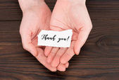 Fotografie cropped shot of woman holding paper with thank you lettering over wooden table