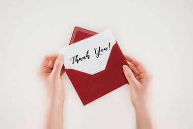 cropped shot of woman opening red envelope with thank you lettering on paper isolated on white