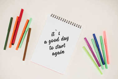 top view of notepad with its a good day to start again lettering and colorful markers isolated on white