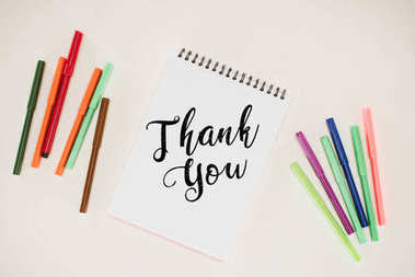 top view of notepad with thank you lettering and colorful markers isolated on white