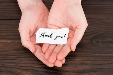 cropped shot of woman holding paper with thank you lettering over wooden table