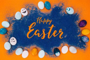 top view of happy easter lettering on blue sand and easter eggs on orange surface