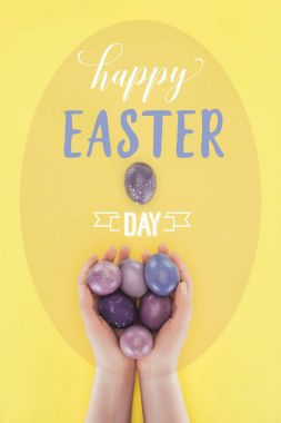 cropped view of woman holding painted easter eggs in hands with happy easter day lettering