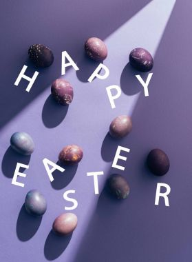 Easter purple eggs with happy easter lettering on purple background with sunbeam