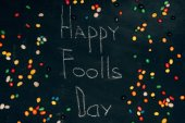 Fotografie flache Lay mit Süßigkeiten und glücklich Foolls Tag Schriftzug auf schwarzem Tischplatte