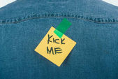 Photo close up view of note with kick me lettering on jeans shirt, april fools day concept