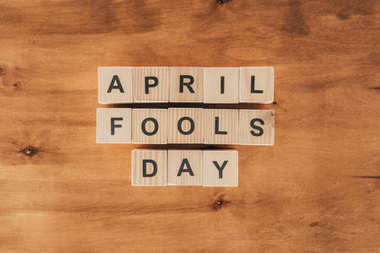 top view of arranged wooden cubes in april fools day lettering on wooden tabletop, 1 april holiday concept