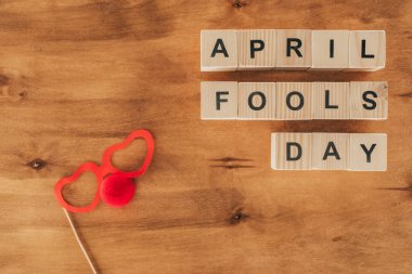 top view of arranged wooden cubes in april fools day lettering with party eyeglasses and clown nose on wooden tabletop, 1 april holiday concept