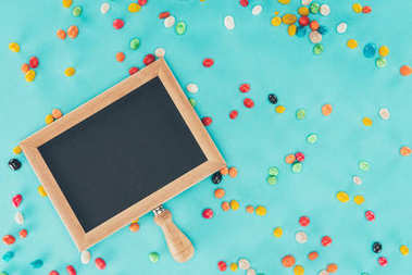 flat lay with empty blackboard and sweets isolated on blue surface, april fools day concept