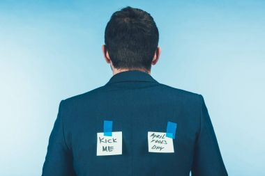 back view of businessman in suit notes with lettering on back, april fools day concept