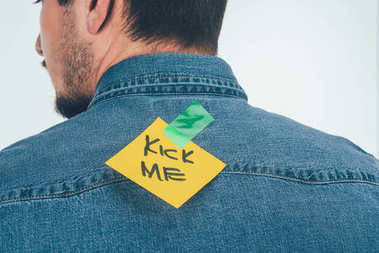 back view of man with note on sticky tape with kick me lettering on back, april fools day holiday concept