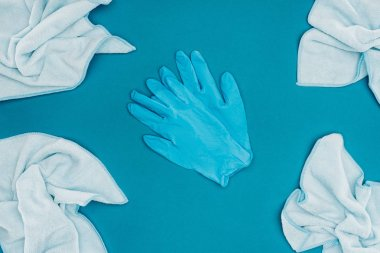 top view of rubber gloves and rags isolated on blue