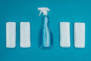 top view of rags and spray bottle isolated on blue