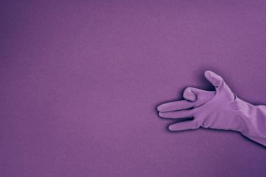 cropped image of woman showing sign with hand in rubber protective glove isolated on violet