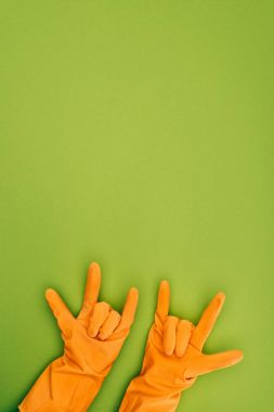 cropped image of woman showing rock signs in rubber protective gloves isolated on green