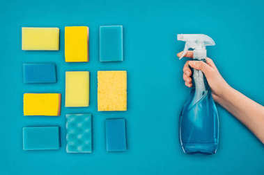 cropped image of woman holding spray bottle near washing sponges isolated on blue