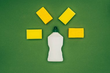 top view of washing sponges and cleaning fluid isolated on green