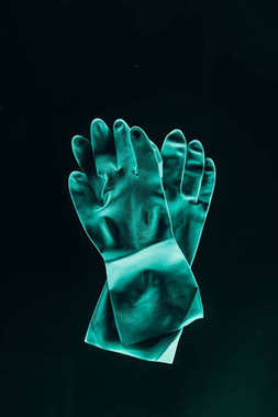 top view of protective rubber turquoise gloves isolated on black