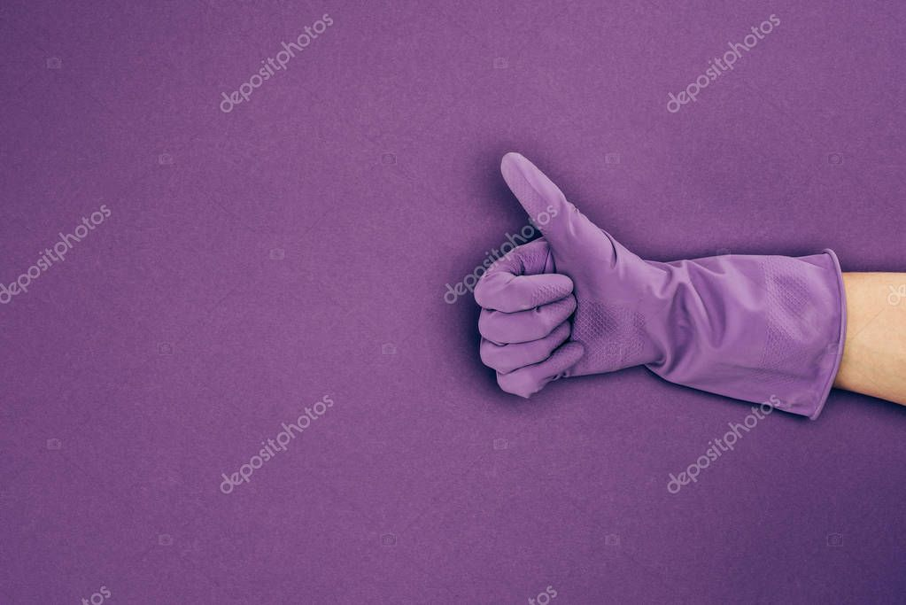 cropped image of woman showing thumb up in rubber protective glove isolated on violet