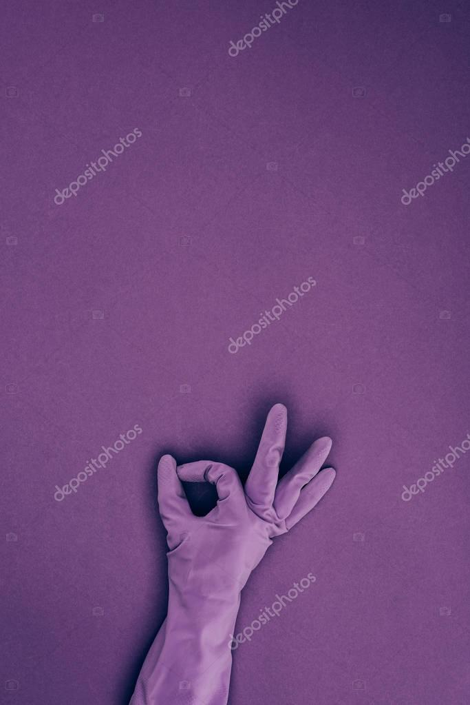 cropped image of woman showing ok sign in rubber protective glove isolated on violet