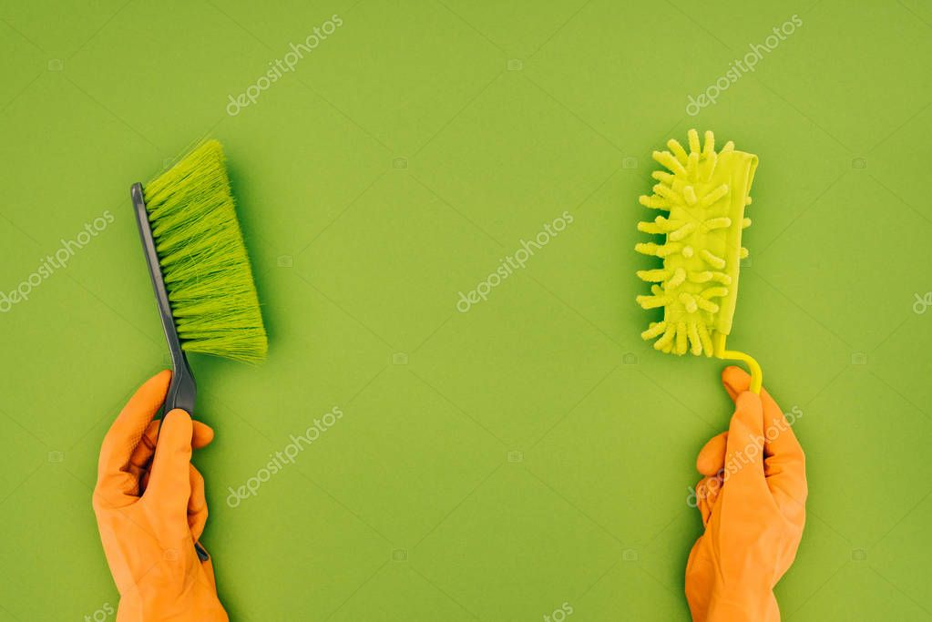Cropped image of woman holding two different cleaning brushes in hands isolated on green