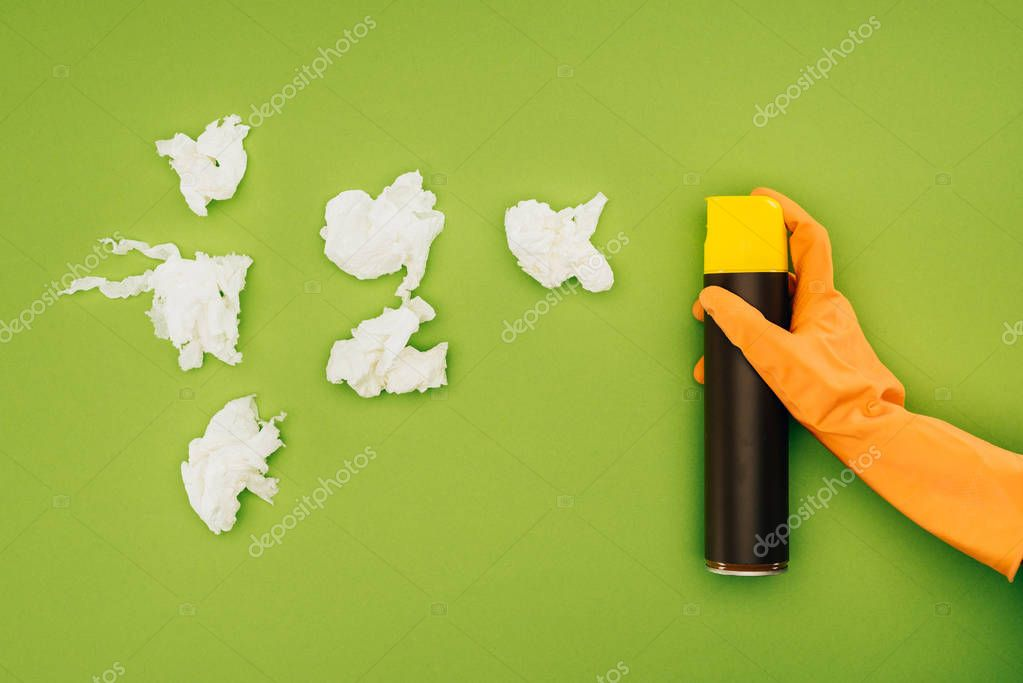 Cropped image of woman holding spray bottle near pieces of crumpled napkins isolated on green