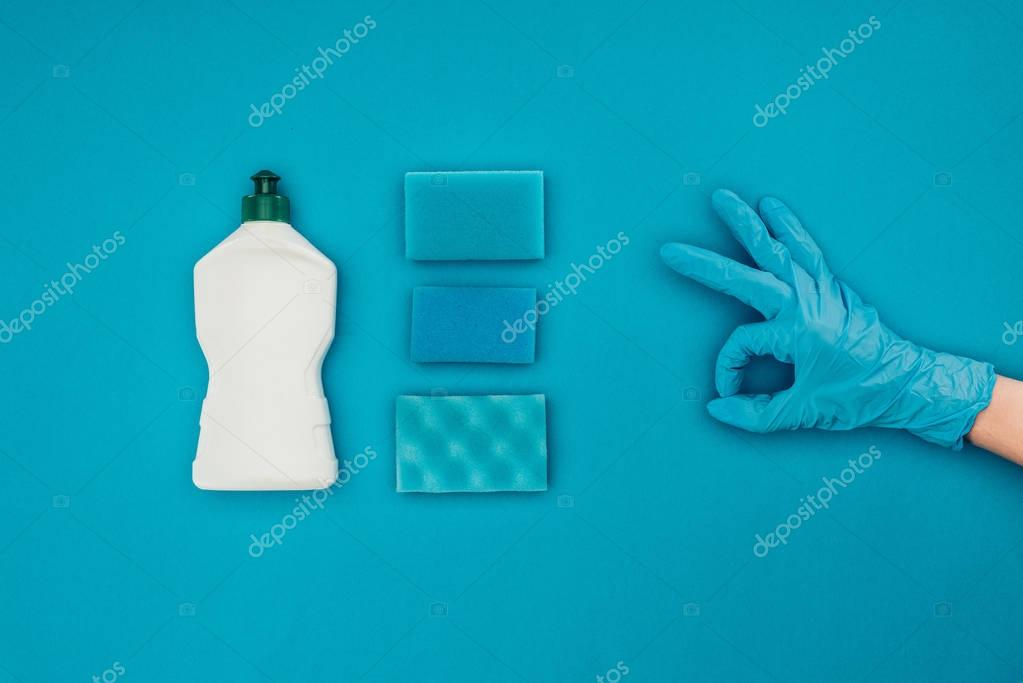 cropped image of woman showing ok sign in rubber protective glove isolated on blue