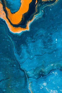 close up of abstract texture with blue and orange oil paint
