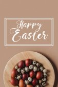 Fotografie top view of easter eggs on wooden plate with Happy Easter inscription