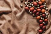 Fotografie Draufsicht des Osterfestes bemalten Eiern und Wachteleiern auf Leinen Tischdecke mit Textfreiraum