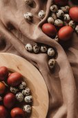 plochý ležela s velikonoční malované a Křepelčí vejce na dřevěné desce