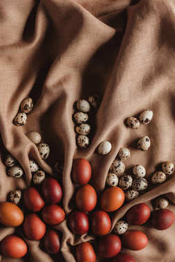 food composition with easter chicken eggs and quail eggs on linen tablecloth