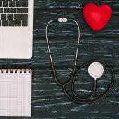 Fényképek felülnézet rendezett laptop, üres jegyzetfüzet, piros szív és sztetoszkóp, a sötét fából készült asztali