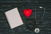Fotografie plochý ležela s uspořádané červené srdce, stetoskop a prázdný poznámkového bloku na tmavé dřevěné stolní, světový den koncepce zdraví