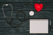 flat lay with arranged red heart, stethoscope and empty notebook on dark wooden tabletop, world health day concept