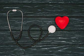 flache Liege mit rotem Herz und Stethoskop auf dunkler Holzplatte, Konzept zum Weltgesundheitstag