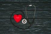 plochý ležel s červeným srdcem a stetoskop na tmavé dřevěné stolní, světový den koncepce zdraví