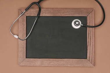 top view of blank chalkboard and stethoscope isolated on beige surface, world health day concept