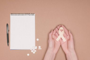 cropped shot of female hands with ribbon, pills and empty notebook isolated on beige tabletop, world health day concept