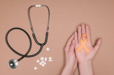 cropped shot of female hands with leukemia, kidney cancer, multiple sclerosis RSD awareness ribbon, pills and stethoscope isolated on beige tabletop