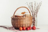 Fotografie basket with easter cakes, painted eggs and catkins on grey
