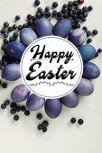 fialové malované vejce kuřete, borůvky a šťastné Velikonoce nápis na grey