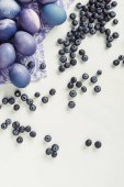 Fotografie top view of violet easter eggs on napkin and blueberries on grey
