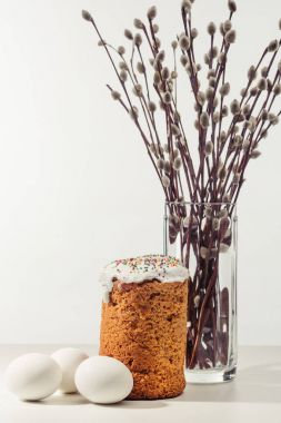 close-up view of chicken eggs, homemade easter cake and willow twigs in vase on grey