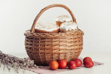 close-up view of basket with easter cakes, painted eggs and catkins on grey