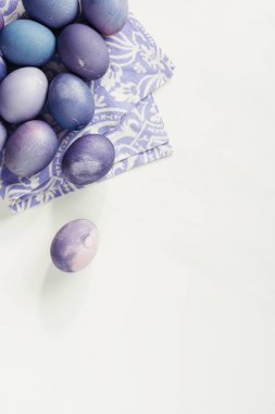 Top view of purple painted easter eggs with napkin on grey stock vector
