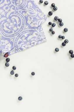 top view of decorative violet napkin and fresh blueberries on grey