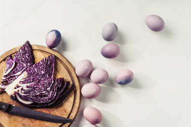 top view of violet painted eggs and purple cabbage with knife on wooden cutting board on grey